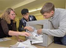 Члены избирательной комиссии вскрывают бюллетени на участке во Владивостоке 4 декабря 2011 года. Россия в воскресенье голосует на выборах в Госдуму, которые правящая верхушка рассматривает как вотум о доверии курсу вновь метящего в президенты премьера Владимира Путина, а оппоненты - как предпоследний шанс пошатнуть его десятилетнюю политическую монополию ненасильственными методами. REUTERS/Yuri Maltsev