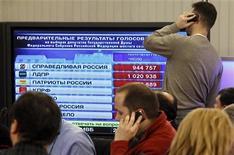 Журналисты и наблюдатели смотрят на экран, отображающий предварительные результаты выборов в Государственную думу РФ, в здании Центральной избирательной комиссии в Москве 4 декабря 2011 года. В воскресенье в России прошли парламентские выборы. REUTERS/Sergei Karpukhin