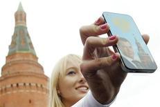 """Участница группы """"Medvedev girls"""" показывает подарок президенту РФ Дмитрию Медведеву в его день рожденья, 14 сентября 2011 года. Хакерские атаки утром дня выборов в России обрушили несколько информационных площадок в интернете, включая сайты """"Эха Москвы"""" и правозащитной организации """"Голос"""", что редакторы связали с публикацией информации о нарушениях избирательного законодательства. REUTERS/Denis Sinyakov  (RUSSIA - Tags: POLITICS SOCIETY)"""