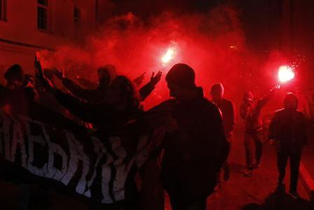 Anarchists burn flares and hold a banner during a protest after voting closed in Russia's parliamentary election in central Moscow, December 4, 2011.  REUTERS/Denis Sinyakov