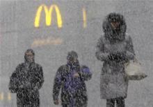 Люди идут по улице под сильным снегом в Москве, 11 ноября 2011 года.  Оставшееся после выходных в Москве потепление сойдет на нет к концу наступившей рабочей недели - температура опустится ниже нуля и пойдет снег, ожидают синоптики. REUTERS/Anton Golubev