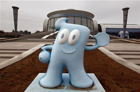 An advertising mascot stands in front of the unopened Ordos exhibition centre in the Kangbashi district of the town of Ordos in China's Inner Mongolia Autonomous Region May 11, 2011. REUTERS/David Gray