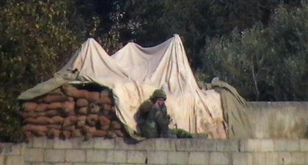 A soldier is seen on a building in Hula near Homs December 1, 2011. Picture taken December 1, 2011. REUTERS/Handout