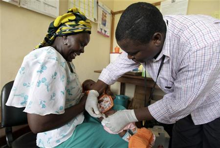Iren Salama (L) holds her baby Pendo as it is given an injection as part of a malaria vaccine trial at a clinic in the Kenya coastal town of Kilifi, November 23, 2010. REUTERS/Joseph Okanga