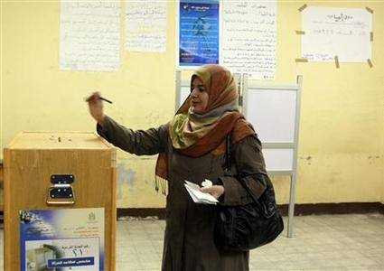 A woman casts her vote during the first day of the parliamentary run-off election in Cairo December 5, 2011.  REUTERS/Asmaa Waguih