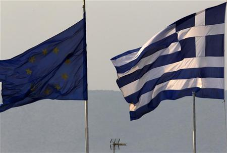 A Greek (R) and an EU flag fly over the Greece's Finance Ministry in Athens November 3, 2011.  REUTERS/Yannis Behrakis