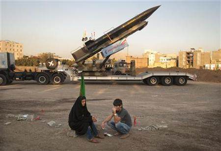 An Iranian couple rests as they sit in front of an Iranian-made Zelzal missile at a war exhibition held by Iran's revolutionary guard to mark the anniversary of the Iran-Iraq war (1980-88), also known in Iran as the ''Holy Defence'', in southern Tehran, September 26, 2011. REUTERS/Morteza Nikoubazl