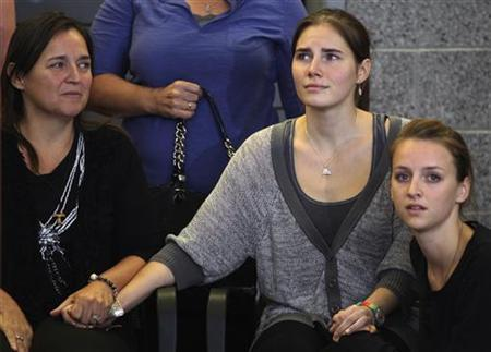 Amanda Knox (C) holds hands with her mother Edda Mellas (L) and her younger sister Deanna Knox (R) at a news conference at Sea-Tac International Airport, Washington after landing there on a flight from Italy, October 4, 2011. REUTERS/Anthony Bolante/Files