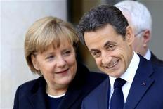 Канцлер Германии Ангела Меркель (слева) вместе с президентом Франции Николя Саркози покидают Елисейский дворец в Париже 5 декабря 2011 года. Лидеры Франции и Германии в понедельник согласовали общий план ужесточения бюджетной дисциплины в еврозоне, заявив, что для быстрого выхода из кризиса необходимо изменить соглашение Евросоюза. REUTERS/Charles Platiau