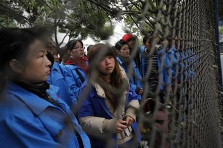 Workers from Hi-P International, who are on strike, stand next to the fence after police entered the factory with trucks to remove heavy machinery, at a suburban area of Shanghai December 6, 2011. REUTERS/Carlos Barria