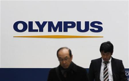 Pedestrians walk past a signboard of Olympus Corp at its showroom in Tokyo December 6, 2011. REUTERS/Kim Kyung-Hoon