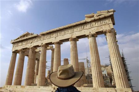 A tourist stands in front of the Parthenon Temple at the archaeological site of the Acropolis Hill in Athens November 3, 2011.  REUTERS/John Kolesidis (