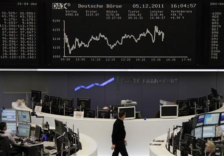 Traders are pictured at their desks in front of the DAX board at the Frankfurt stock exchange December 5, 2011. REUTERS/Remote/Kirill Iordansky