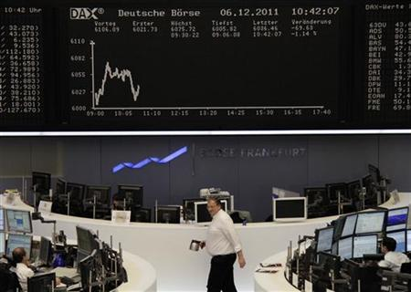 Traders are pictured at their desks in front of the DAX board at the Frankfurt stock exchange December 6, 2011. REUTERS/Remote/Amanda Andersen