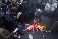 Protesters burn a British flag taken down from the British embassy in Tehran November 29, 2011.   REUTERS/Raheb Homavandi