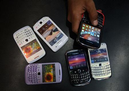 A salesman displays a Blackberry mobile phone to customers next to dummy handsets at a shop in Jammu October 13, 2011. REUTERS/Mukesh Gupta