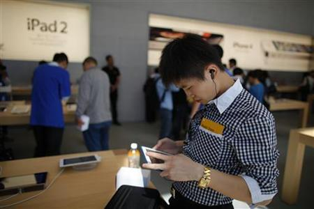 A man looks at an Apple iPad 2 at the company's new store in Nanjing Road, Shanghai September 23, 2011. REUTERS/Aly Song