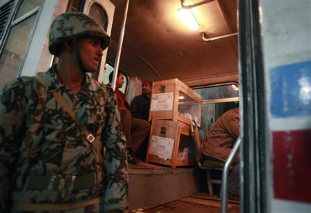 An Egyptian soldier stands guard as members of the election committee sit in a bus with ballot boxes after voting closed, outside a voting center during the second day of the parliamentary run-off elections in Cairo December 6, 2011. REUTERS/Asmaa Waguih