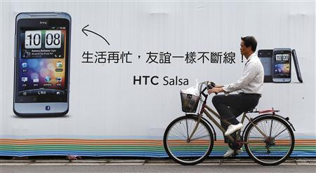 A man cycles past a HTC advertisement in Taipei December 7, 2011. REUTERS/Pichi Chuang