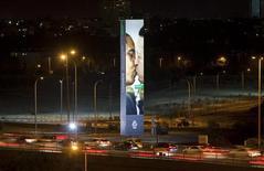 """Плакат компании Benetton с изображением целующихся Барака Обамы и Уго Чавеса возле дороги в Тель-Авиве. Фотография сделана 28 ноября 2011 года. Президент Венесуэлы Уго Чавес назвал рекламные плакаты компании Benetton, на которых он изображен целующимся со свои идейным противником Бараком Обамой, """"хорошей шуткой"""". REUTERS/Nir Elias"""