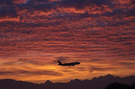 A Brussels Airlines aircraft prepares for landing in Cointrin airport during sunrise over the Mont Blanc in Geneva December 1, 2011.  REUTERS/Denis Balibouse