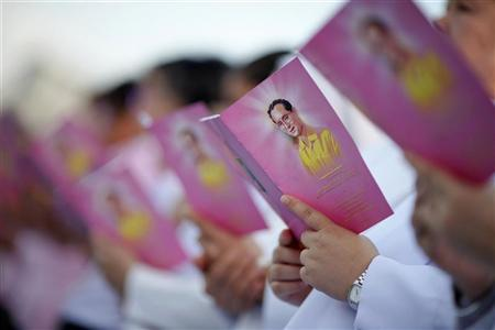 Catholic nuns hold booklets with pictures of Thailand's King Bhumibol Adulyadej as they sing outside the Royal Palace in Bangkok to mark his birthday December 4, 2011. REUTERS/Damir Sagolj
