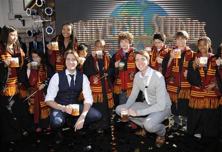 Actors James (L) and Oliver Phelps pose with fans following an announcement of the new ''The Wizarding World of Harry Potter'' attraction to be built at Universal Studios Hollywood in Los Angeles December 6, 2011. REUTERS/Phil McCarten