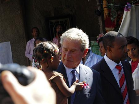 Former President George W. Bush (C) carries an Ethiopian child whose mother is receiving HIV treatment through programmes funded by the President's Emergency Plan for AIDS Relief (PEPFAR), after arriving with his wife former First Lady Laura Bush in the capital Addis Ababa December 4, 2011. Bush launched PEPFAR during his presidency in 2003.            REUTERS/Aron Maasho
