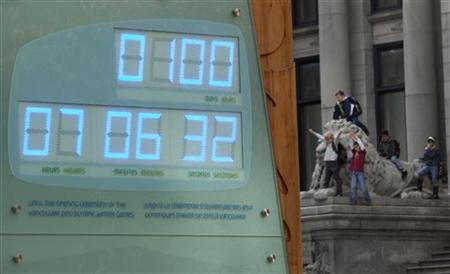 Schoolchildren climb over a nearby statue as the Olympic countdown clock shows 100 days left before the start of the 2010 Olympic Winter in Vancouver, British Columbia November 4, 2009.       REUTERS/Andy Clark
