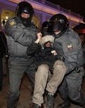 Российская полиция задерживает протестующего у Гостиного двора в Санкт-Петебурге 7 декабря 2011 года. Четвертый день подряд в северной столице проходит по одному и тому же сценарию: 300-400 человек, преимущественно молодежь и школьники, приходят на объявленные в интернете акции протеста и примерно половину за час-полтора забирает полиция.  REUTERS/Alexander Demianchuk (RUSSIA  - Tags: CIVIL UNREST POLITICS)