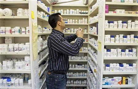 A pharmacist looks through shelving to fill a prescription in New York, December 23, 2009. REUTERS/Lucas Jackson