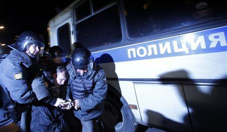 Policemen detain an activist during rally to protest against the results of the parliamentray elections and the policies conducted by Russian authorities in Moscow December 6, 2011.   REUTERS/Anton Golubev