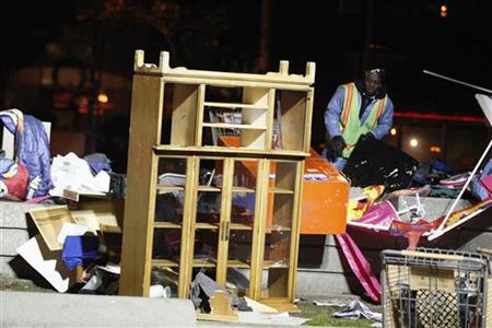 A Department of Public Works worker removes debris from the Occupy San Francisco encampment at Justin Herman Plaza after a morning police raid in San Francisco, California December 7, 2011. REUTERS/Stephen Lam