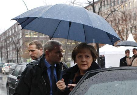 German Chancellor Angela Merkel holds an umbrella as she arrives to the presentation of the first fully functional ''Energy Surplus House'' in Berlin, December 7, 2011.  REUTERS/Fabrizio Bensch