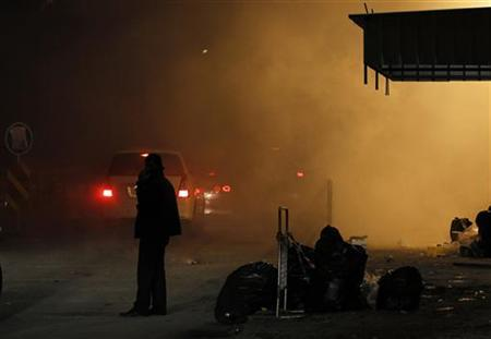 A protester stands along a street engulfed in tear gas smoke after riot police fired it at protesters trying to march to Pearl Square following a Ashura procession, in Daih village, Manama December 7, 2011. REUTERS/ Hamad I Mohammed