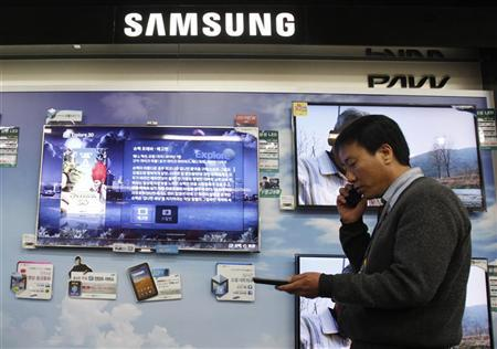 A salesman talks on his mobile phone as he walks past Samsung Electronics' LED television displays at an electronics store in Seoul April 29, 2011.   REUTERS/Truth Leem