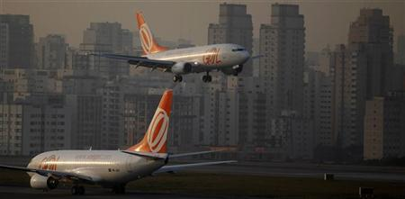 A Brazilian airline Gol aircraft (top) prepares to land at Congonhas airport in Sao Paulo July 11, 2011. REUTERS/Nacho Doce