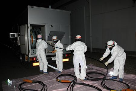 Workers wearing protective suits conduct training to secure electricity with power source car in the nighttime at the tsunami-crippled Fukushima Daiichi nuclear power plant in Fukushima prefecture, in this handout picture taken on December 7, 2011.  REUTERS/Tokyo Electric Power Co./Handout