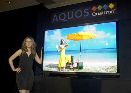 A model stands by a Sharp Quattron 70-inch LCD TV after the television was introduced during a news conference at the 2011 International Consumer Electronics Show (CES) in Las Vegas, Nevada January 5, 2011.  REUTERS/Steve Marcus