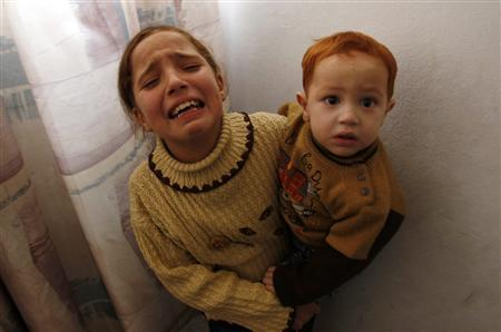 The daughter of militant Eassam Al-Batsh mourns as she holds her brother during their father's funeral in Gaza City, December 8, 2011. REUTERS/Ibraheem Abu Mustafa