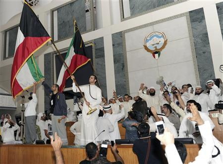 Kuwaiti protesters hold national flags as they stand upon the desks of the speaker of parliament in the debate hall of the National Assembly at the Kuwait's parliament in Kuwait City in this November 16, 2011 file photo.  REUTERS/Stringer/Files UNREST)