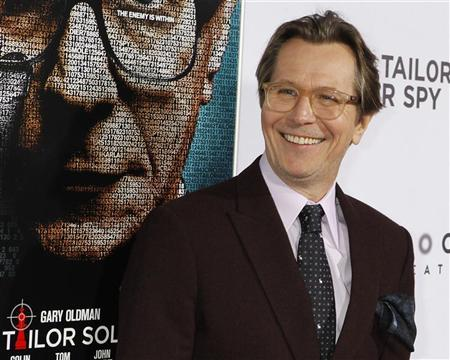 Cast member Gary Oldman poses in front of a poster featuring his character of the film ''Tinker, Tailor, Soldier, Spy'' at the Los Angeles premiere of the movie in Hollywood December 6, 2011. REUTERS/Fred Prouser