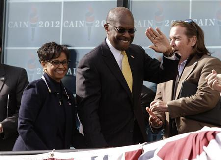 Herman Cain arrives with his wife Gloria at his side to announce that he is ''suspending'' his presidential campaign, in Atlanta, Georgia December 3, 2011. REUTERS/John Adkisson