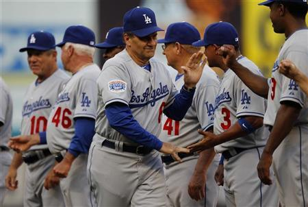 Los Angeles Dodgers manager Joe Torre shakes hands with members of his team before their MLB National League baseball game against the Florida Marlins in Miami, Florida, April 9, 2010. REUTERS/Carlos Barria