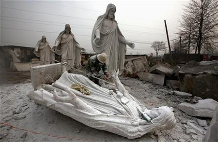 A sculptor works on statues of Jesus Christ at an outdoor workshop in the town of Dangcheng in Quyang county, 240 km (150 miles) southwest of Beijing December 7, 2011. REUTERS/David Gray