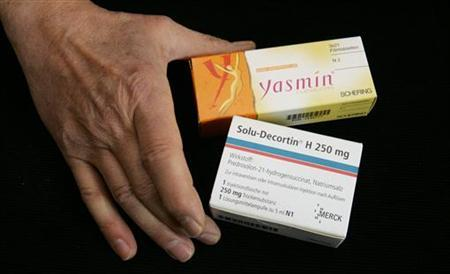 A chemist displays birth control pill 'Yasmin' of German drugmaker Schering and a cortisone of drugs and chemicals group Merck in a Berlin apothecary March 13, 2006.      REUTERS/Fabrizio Bensch