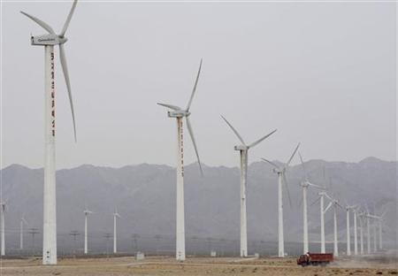 A truck drives past wind turbines at a wind power plant in Qingtongxia, Ningxia Hui Autonomous Region January 18, 2011. REUTERS/Stringer/Files