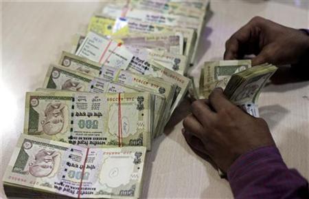 An employee counts Indian currency notes at a cash counter inside a bank in Mumbai June 21, 2010. REUTERS/Rupak de Chowdhuri/Files