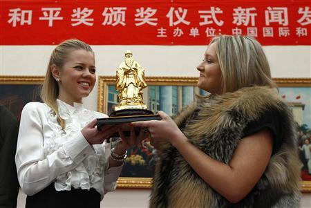 Russian students Ekateryna Dakhova (L) and Maria Ostasheako hold the Chinese Confucius Peace Prize after accepting it on behalf of this year's winner Russian Prime Minister Vladimir Putin in Beijing December 9, 2011.  REUTERS/David Gray