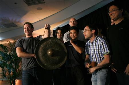 Facebook CEO Mark Zuckerberg (L) holds a gong while celebrating with members of his staff after unveiling the company's new location services feature called ''Places'' during a news conference at the Facebook headquarters in Palo Alto, California, in this August 18, 2010 file photograph. REUTERS/Robert Galbraith/Files